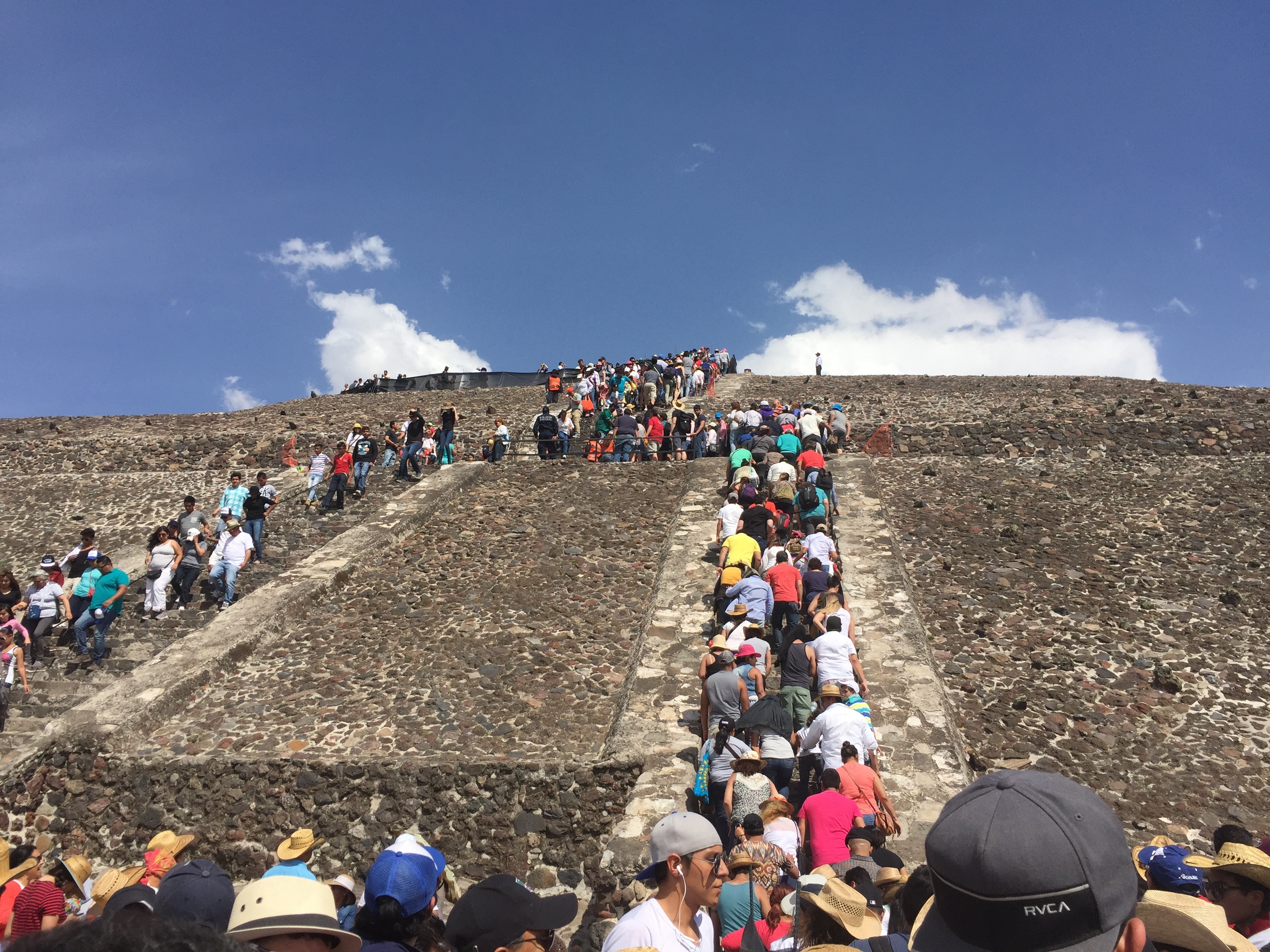 A line of tourists winds up the steps of the pyramid of the sun at Teotihuacan.