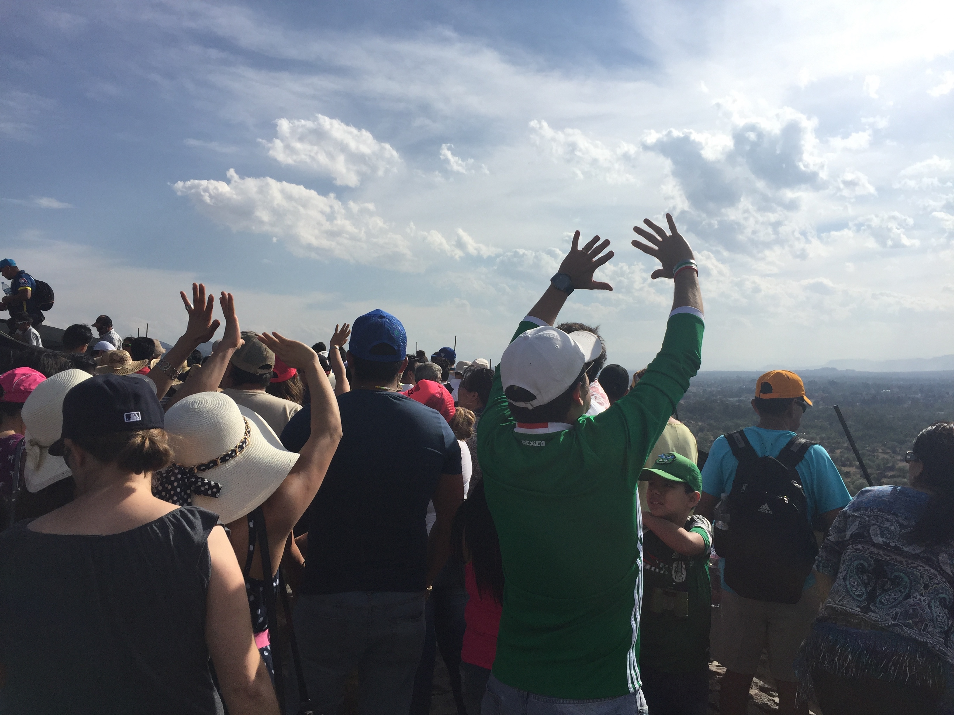 Tourists feel the energy of the sun at the pyramid of the sun in teotihuacan.