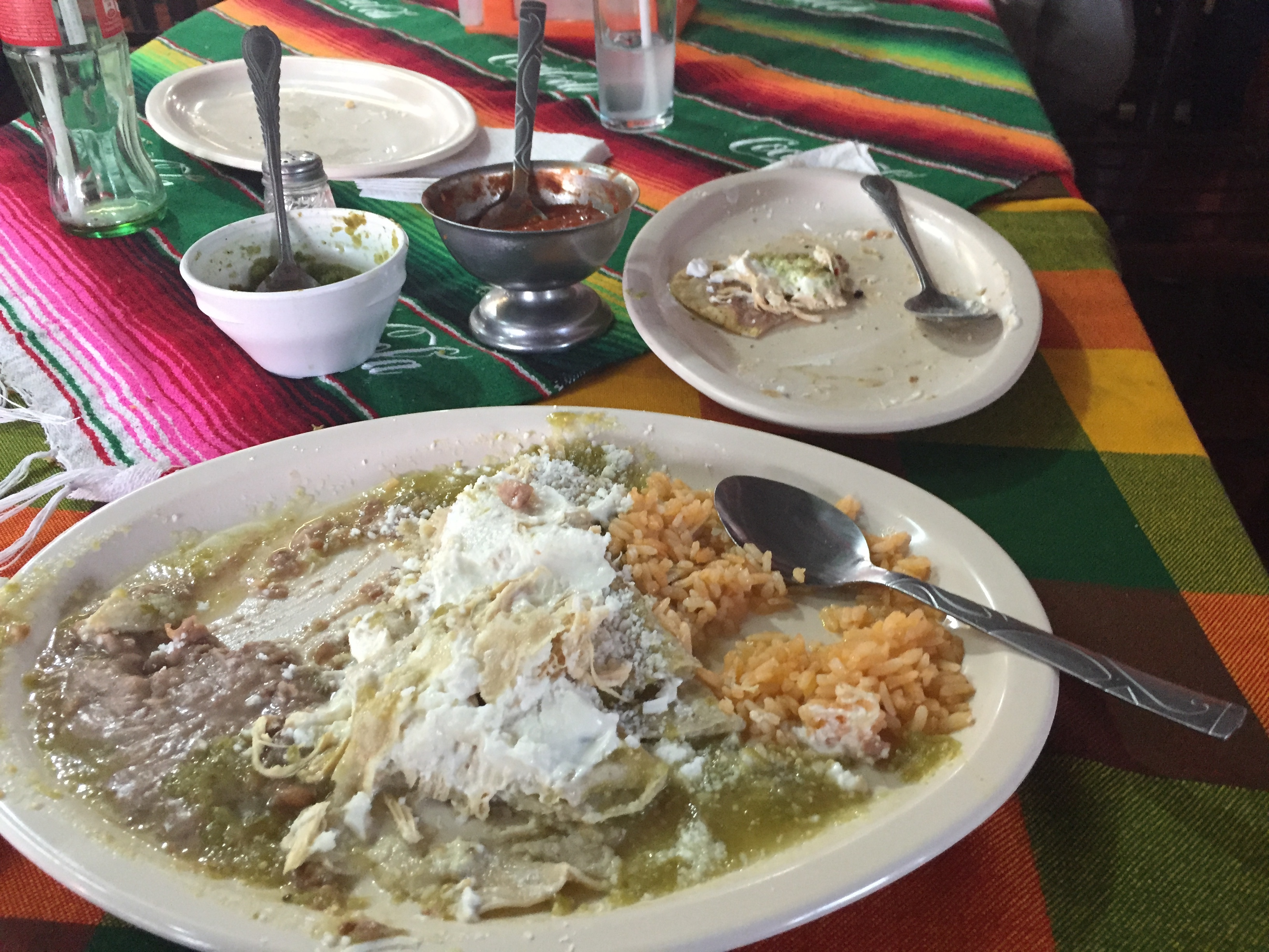 A half eaten plate of Mexican style enchiladas.