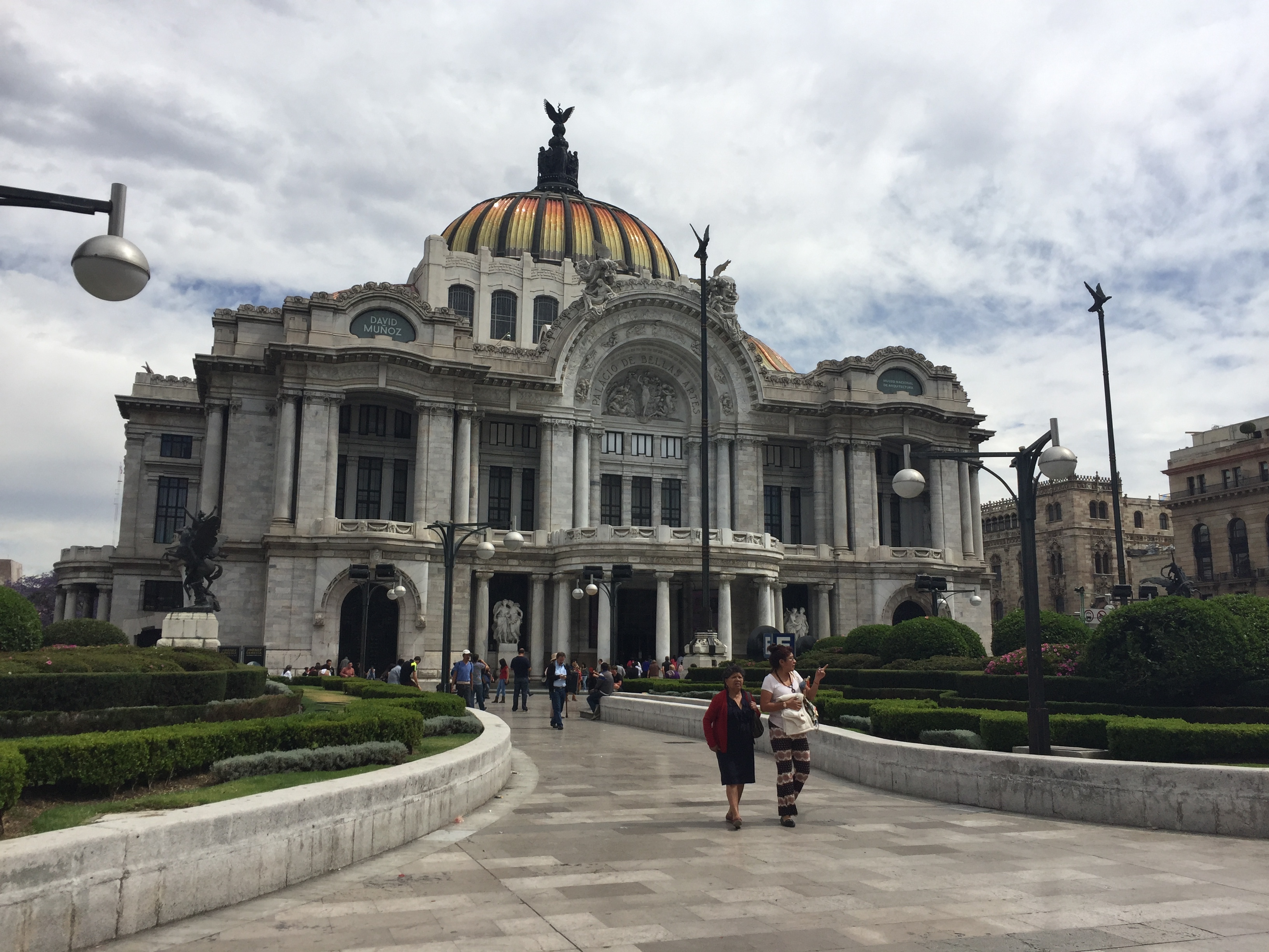 Tourists walk around palacio bellas artes in downtown mexico city.