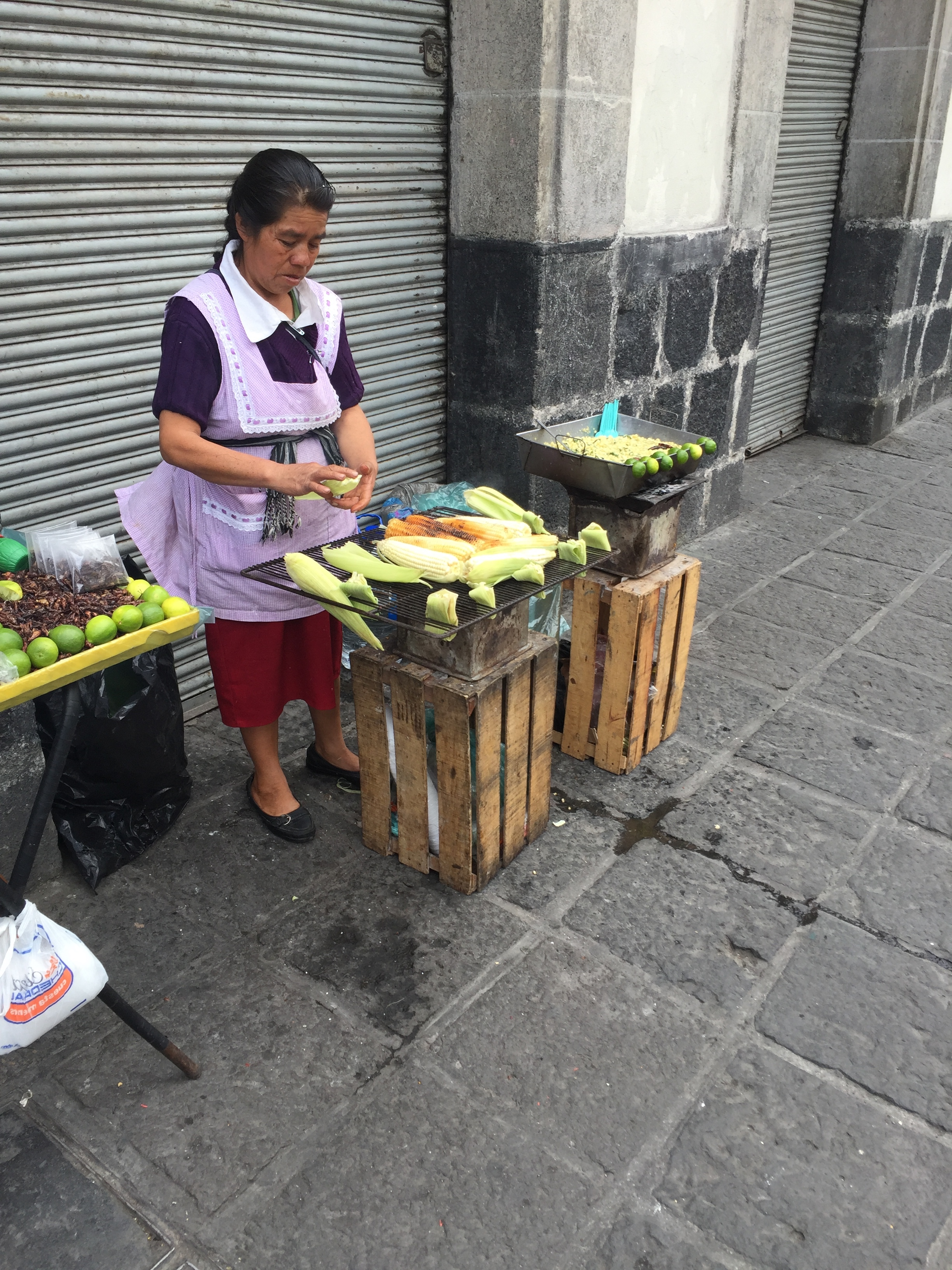 A woman prepares corn on a street in Mexico City.