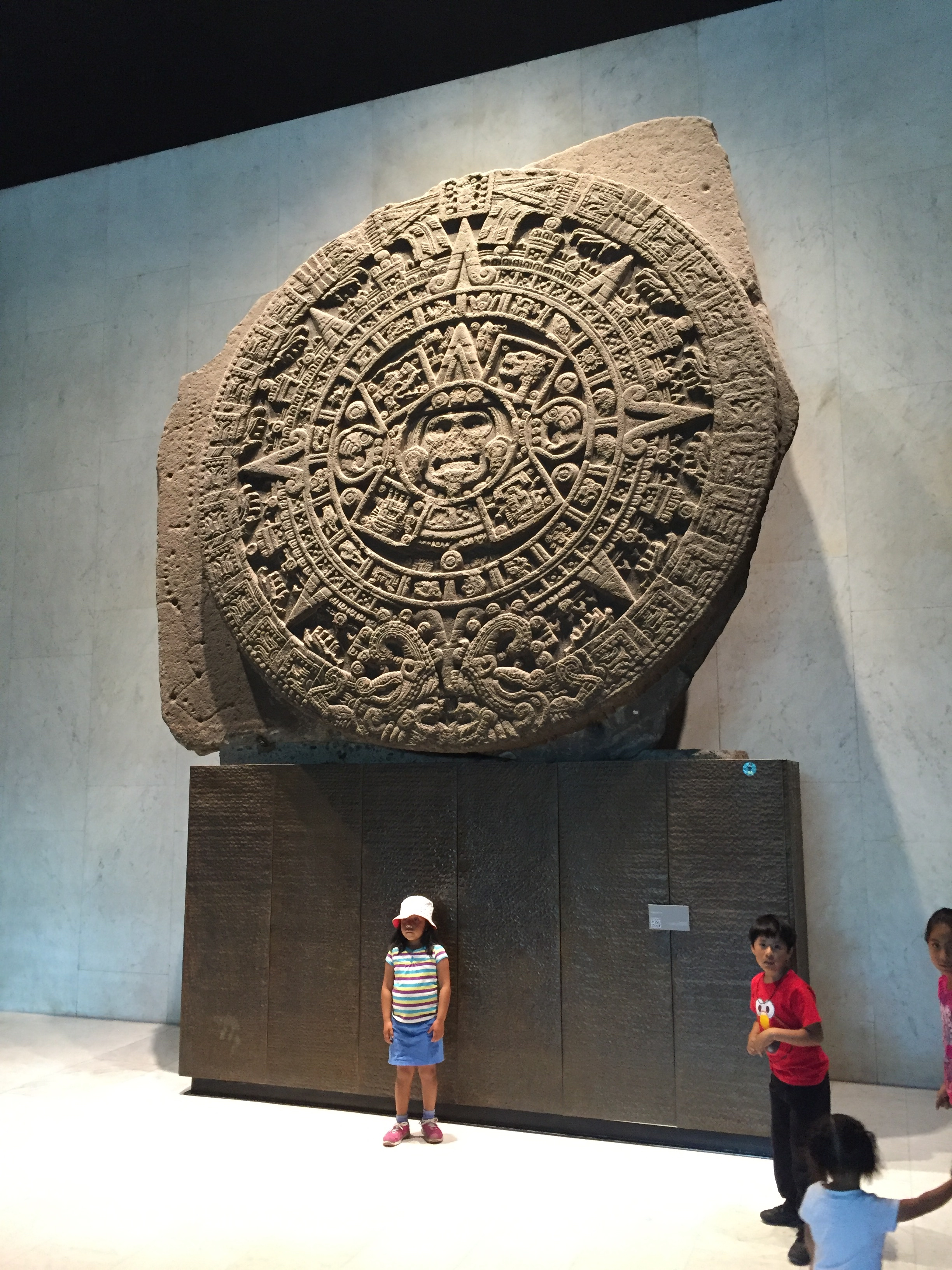 Children pose for photos in front of the Aztec calendar in the Anthropology Museum of Mexico City.