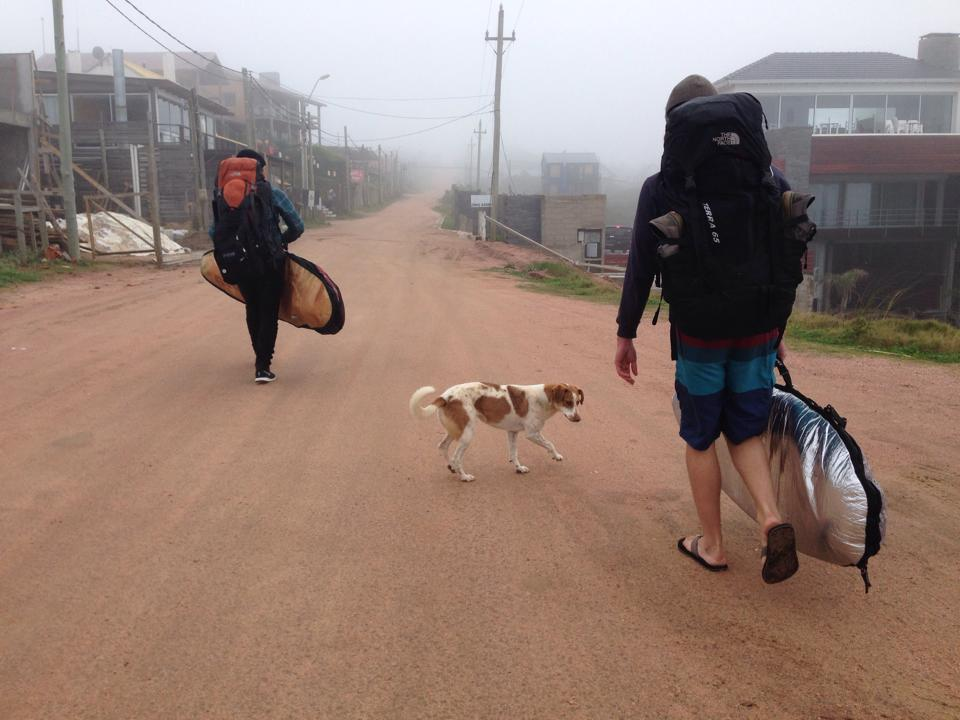Two surfers walk down a dirt road in Uruguay with a stray dog.