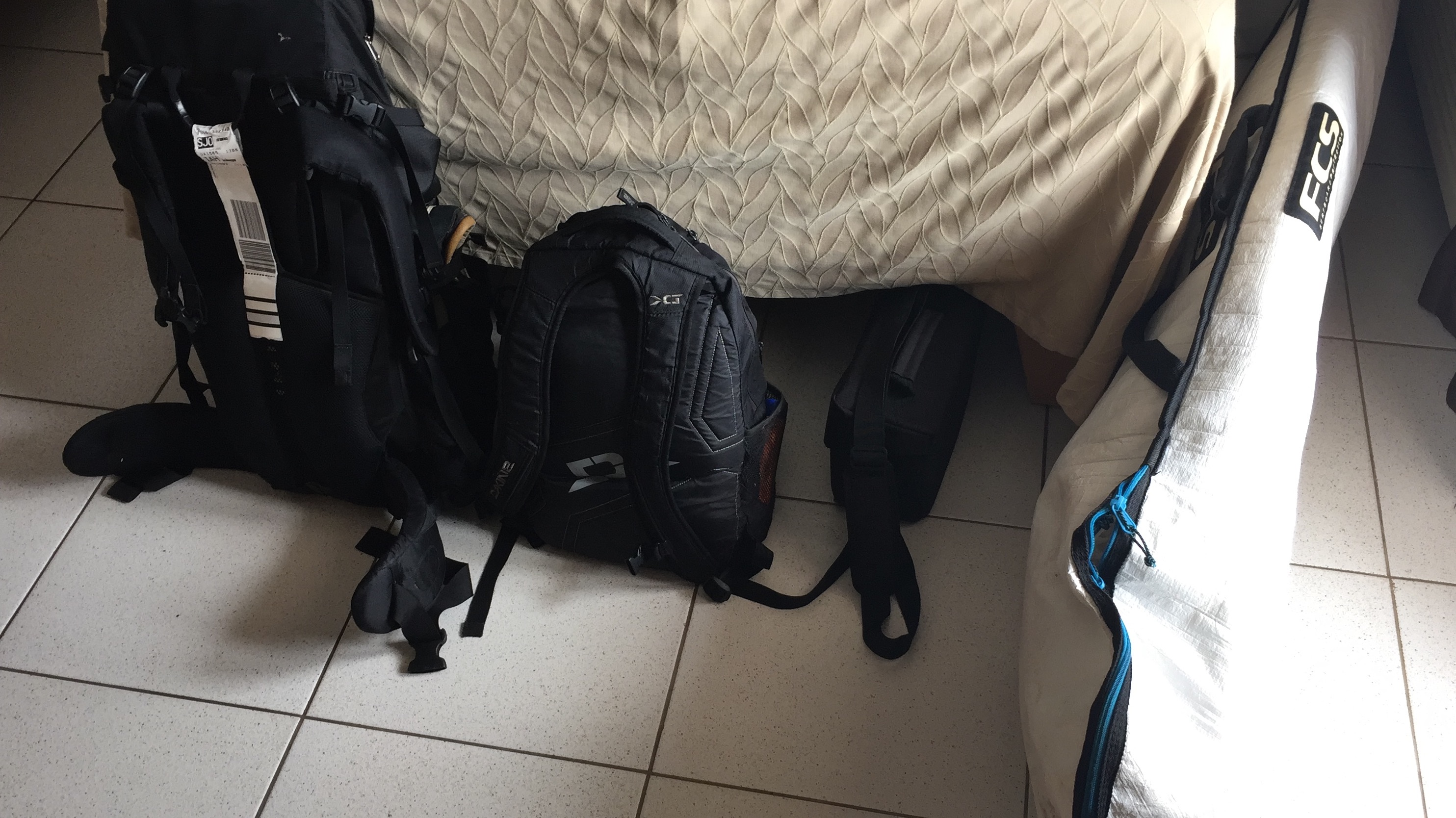 Two backpacks and a surfboard sit on the ground of a hotel room in Costa Rica.
