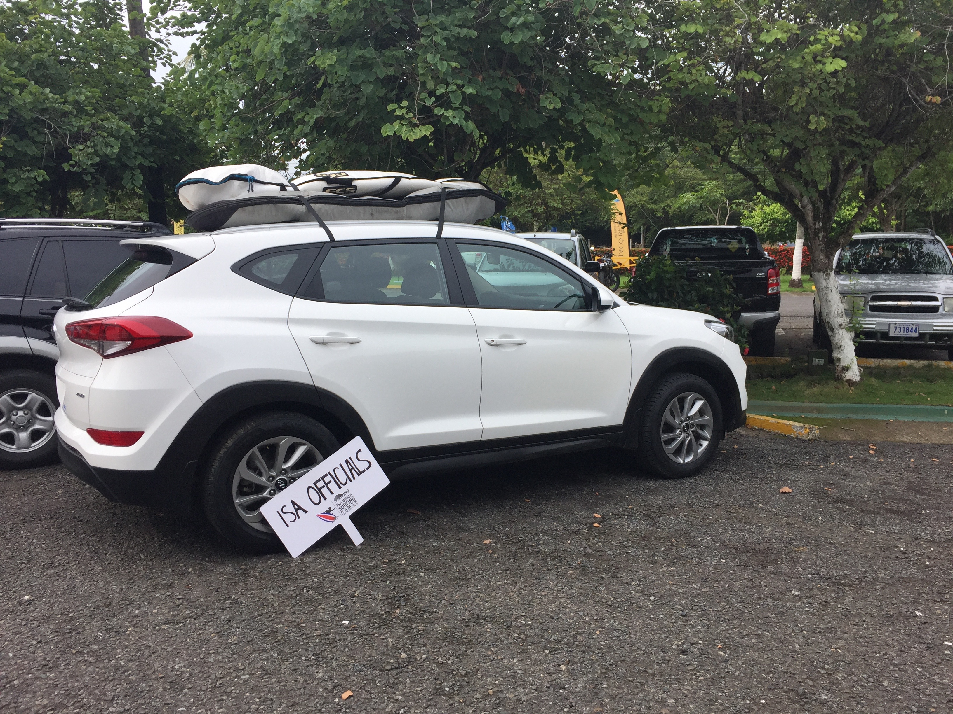 A white SUV sits parked with surfboards strapped on the roof in Costa Rica.