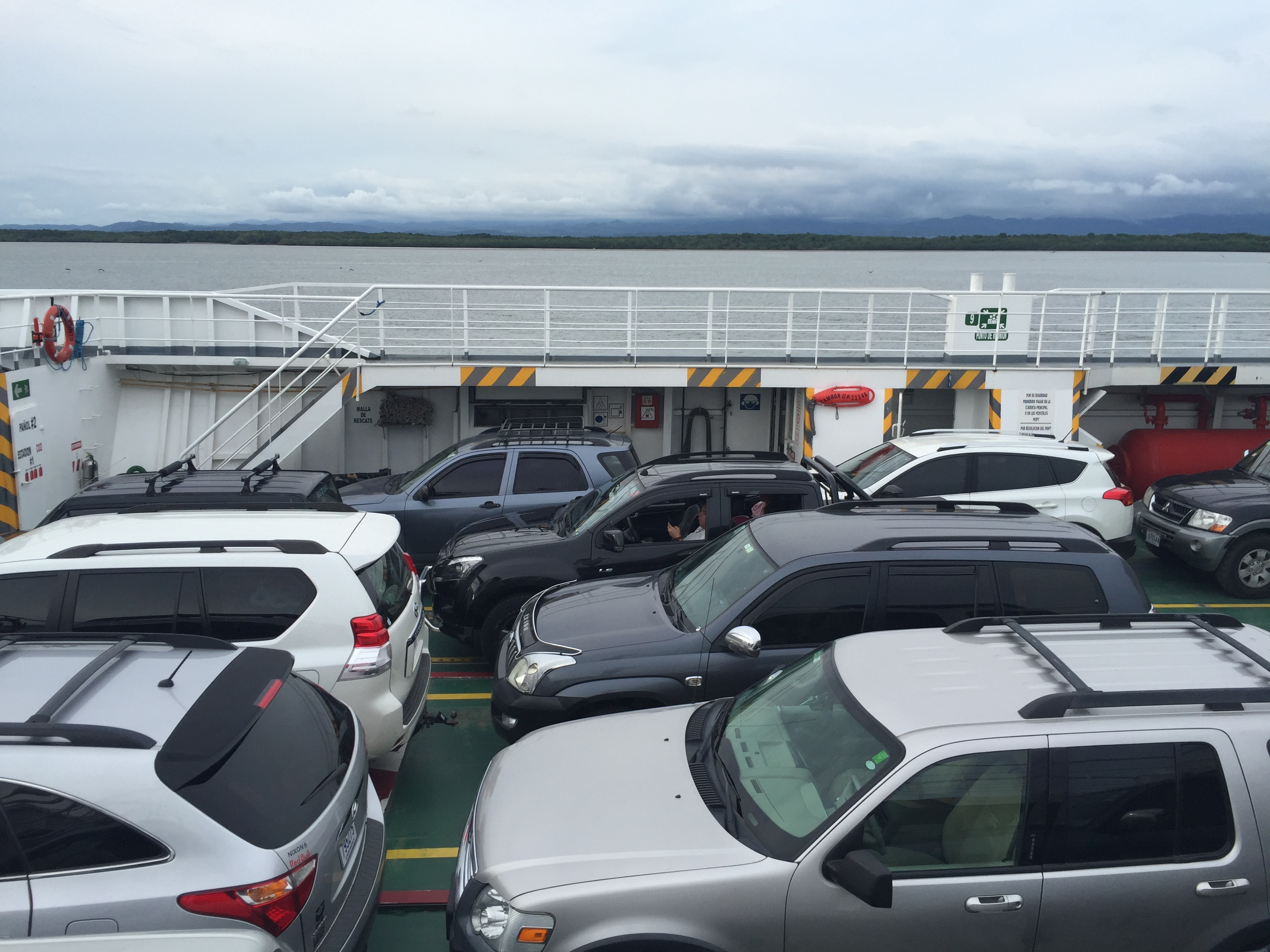 Cars wait on a ferry sailing across a waterway in Costa Rica.