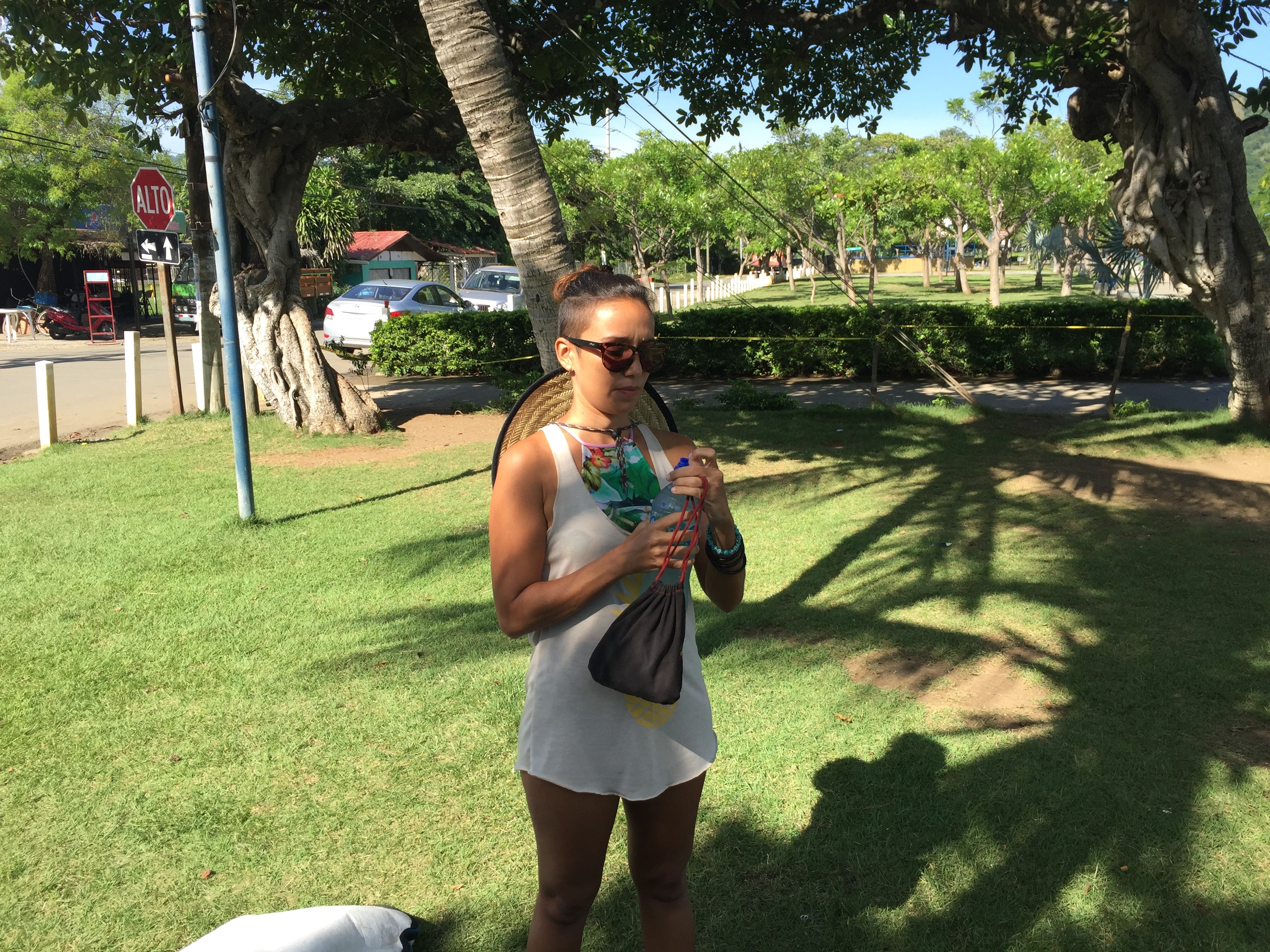 Lois Solano opens a bottle of water on a grass lawn in Costa Rica.