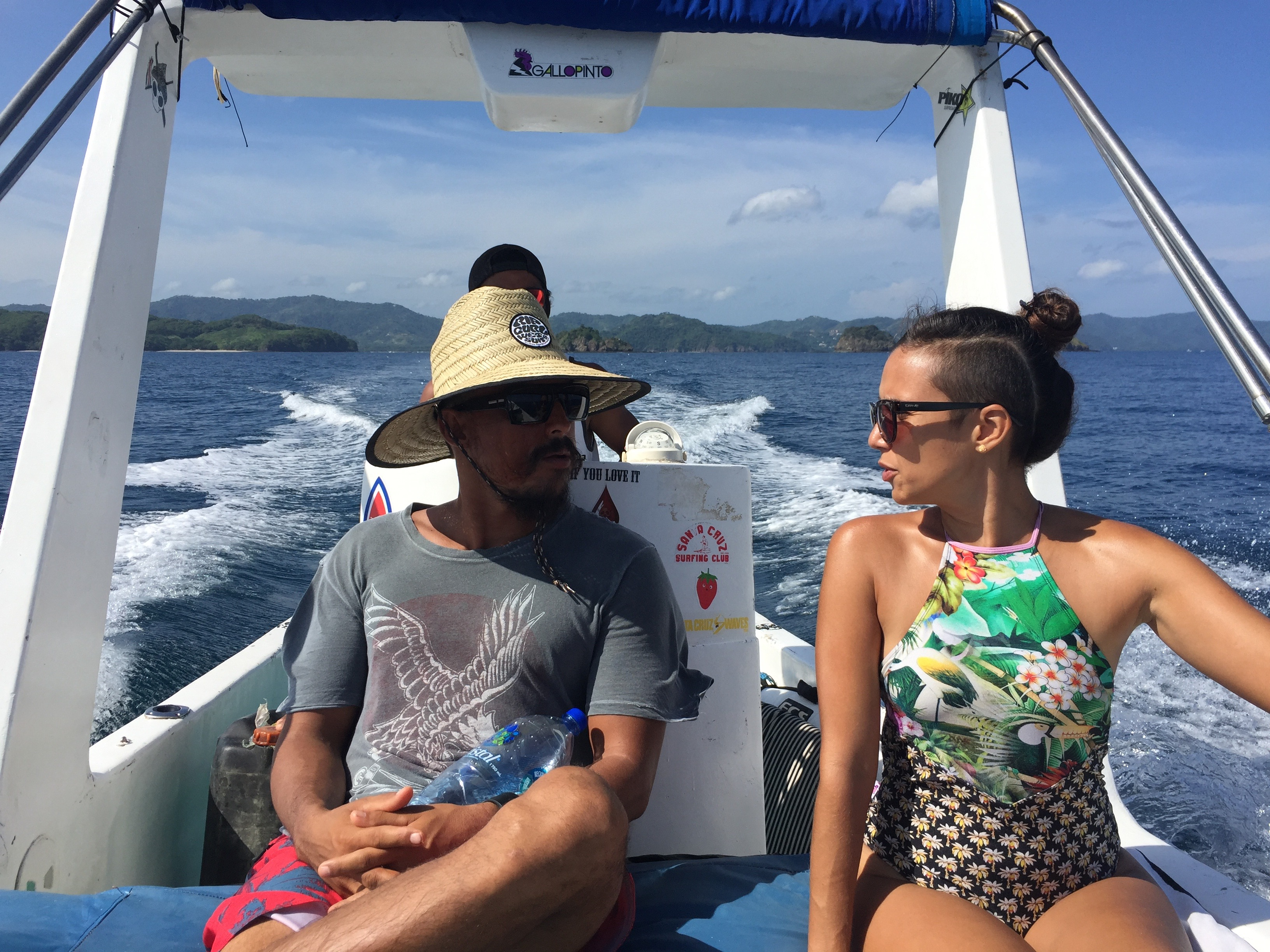 A Costa Rican couple rides a boat to go surfing.