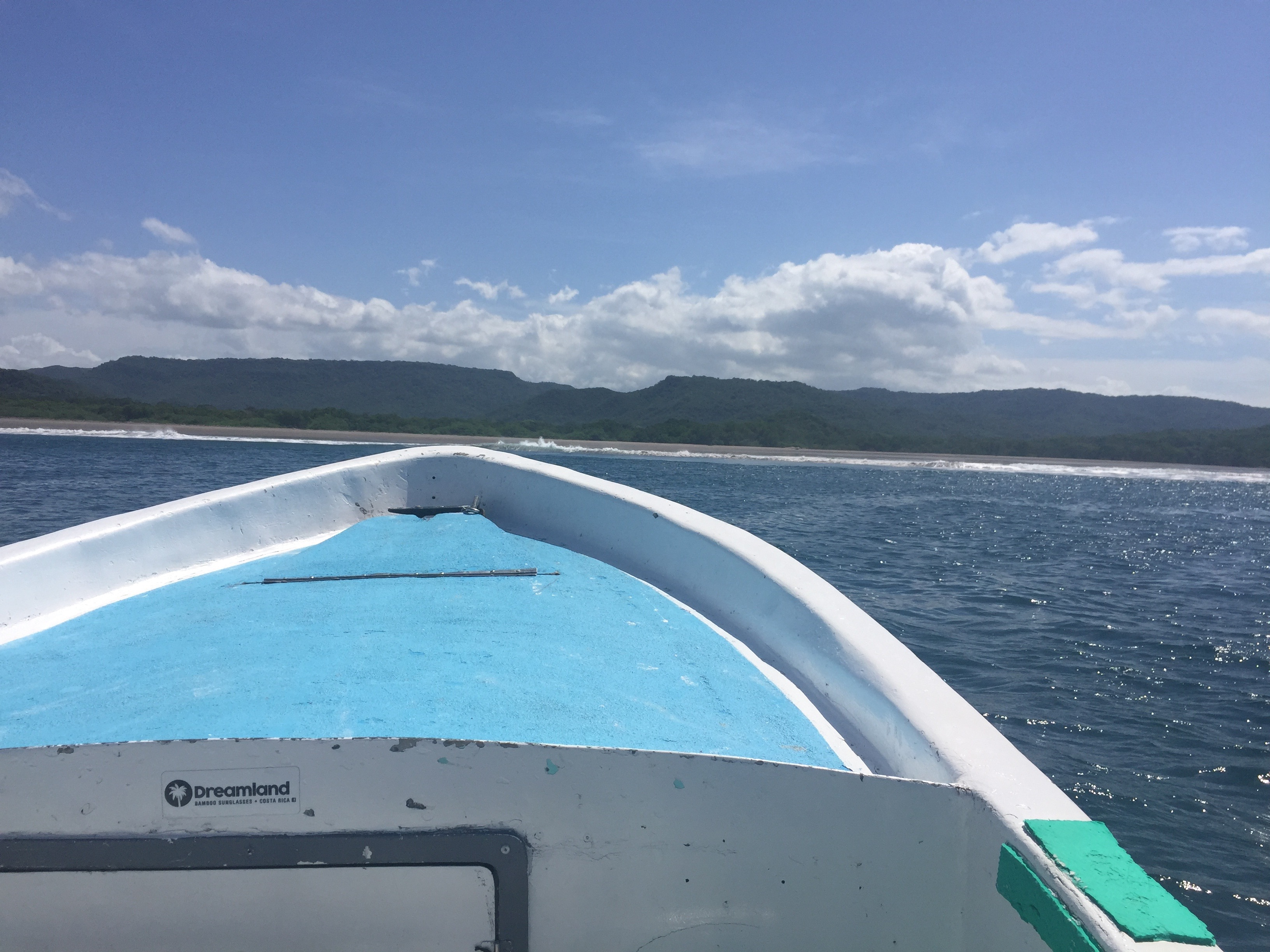 The bow of a boat headed towards a pristine beach in Costa Rica.