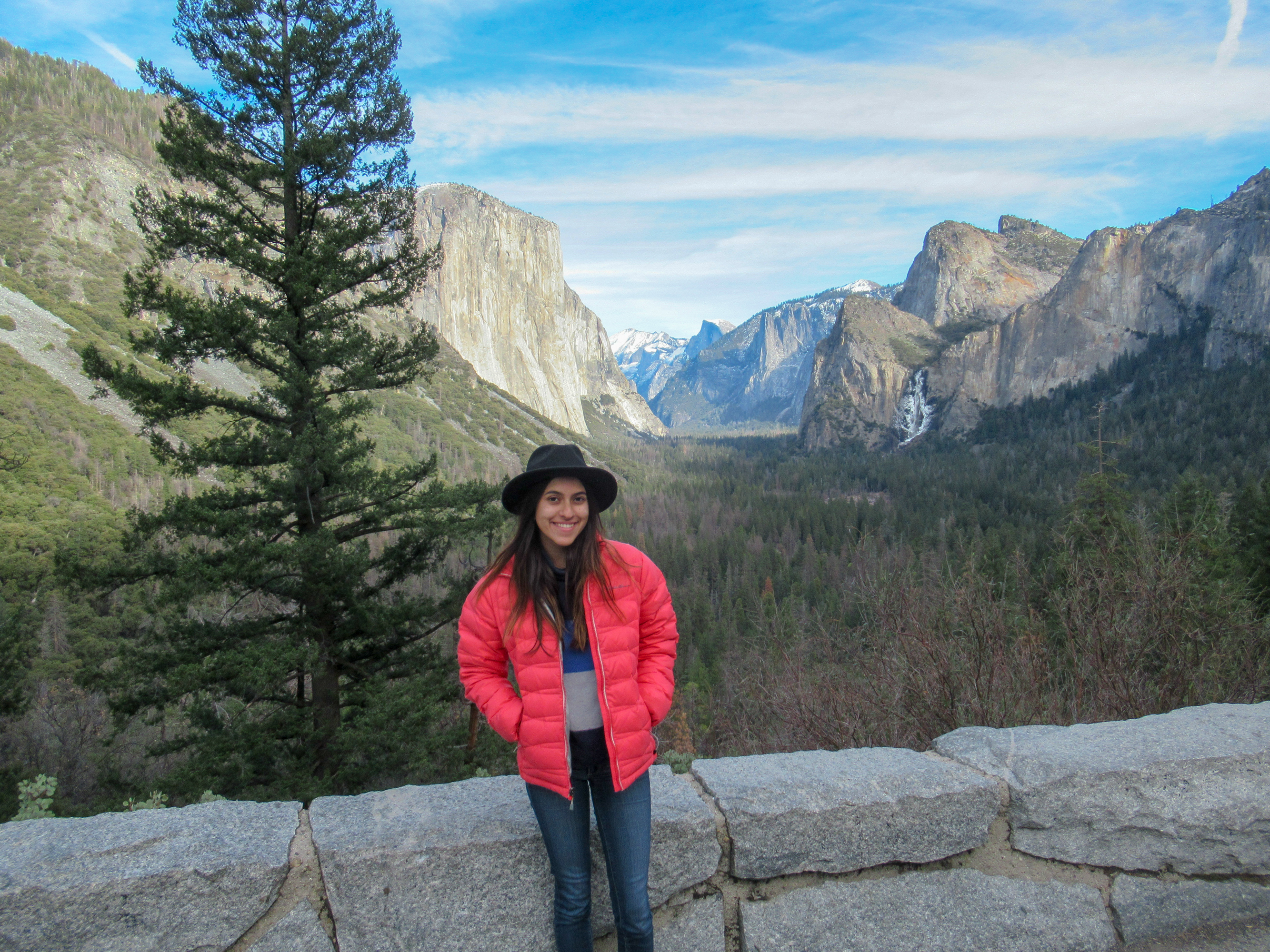 Madison Snively sits on a ledge at an overlook of Yosemite Valley.