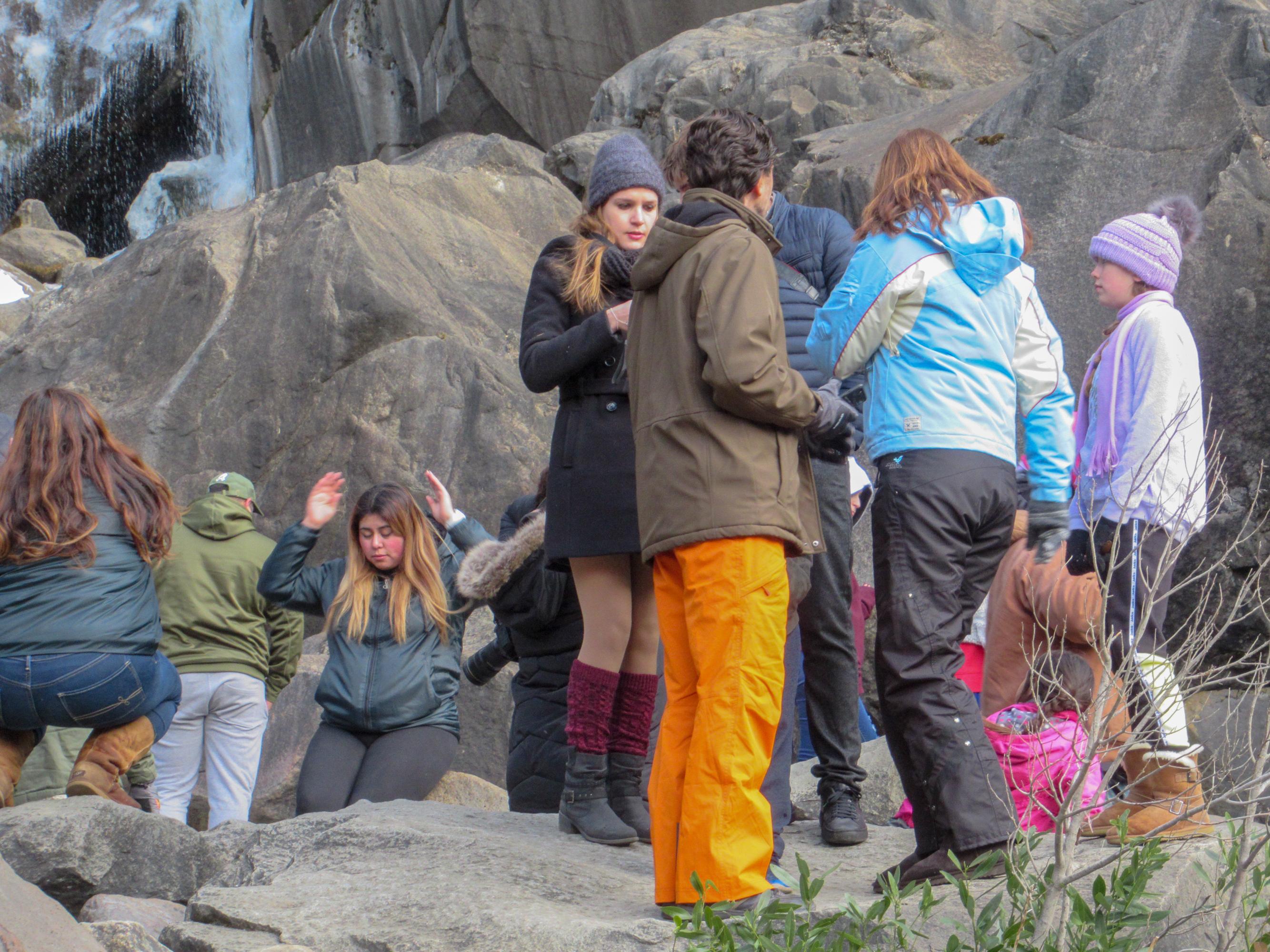 Tourists climb on rocks at the base of bridalveil falls.