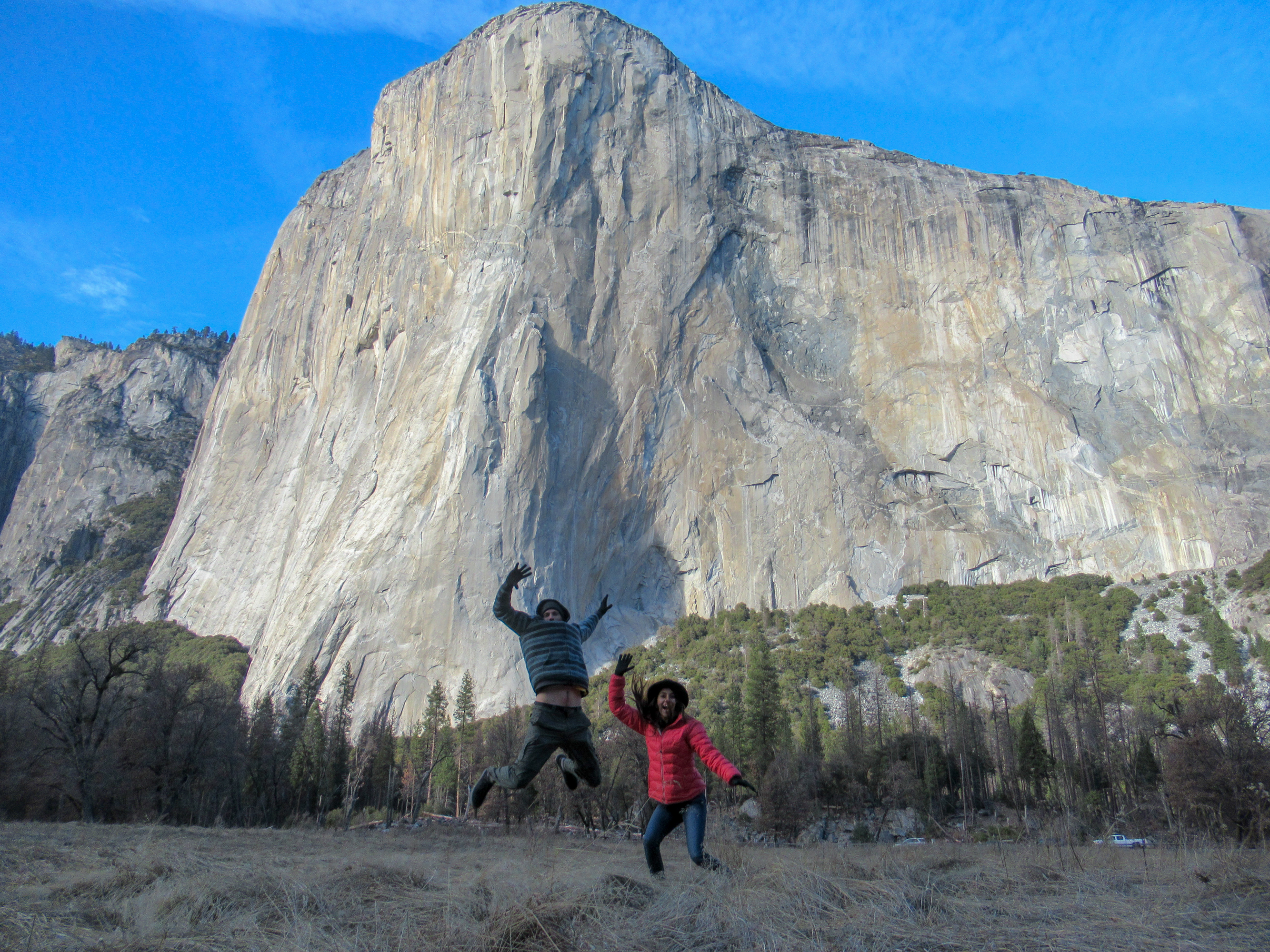 A couple jumps for a photo in front of El Capitan.
