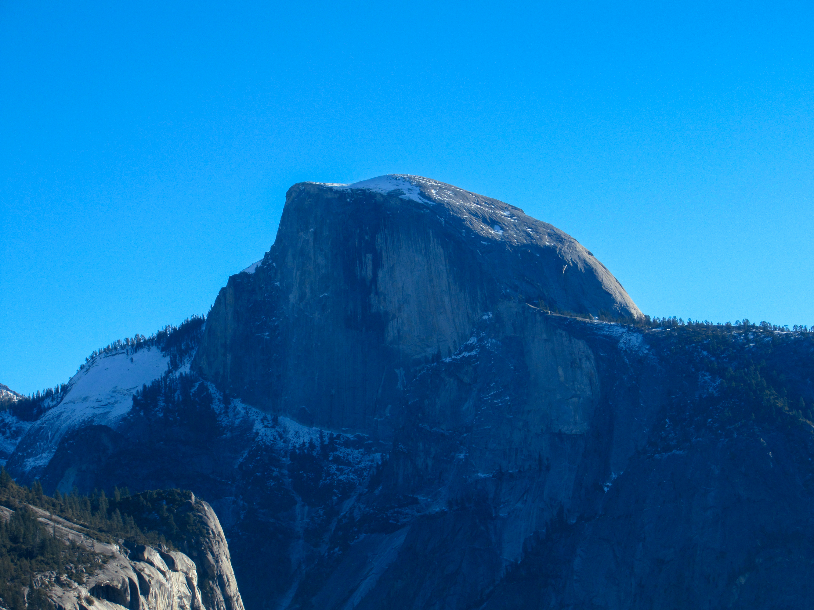 The morning sun shines on the back of Half Dome.