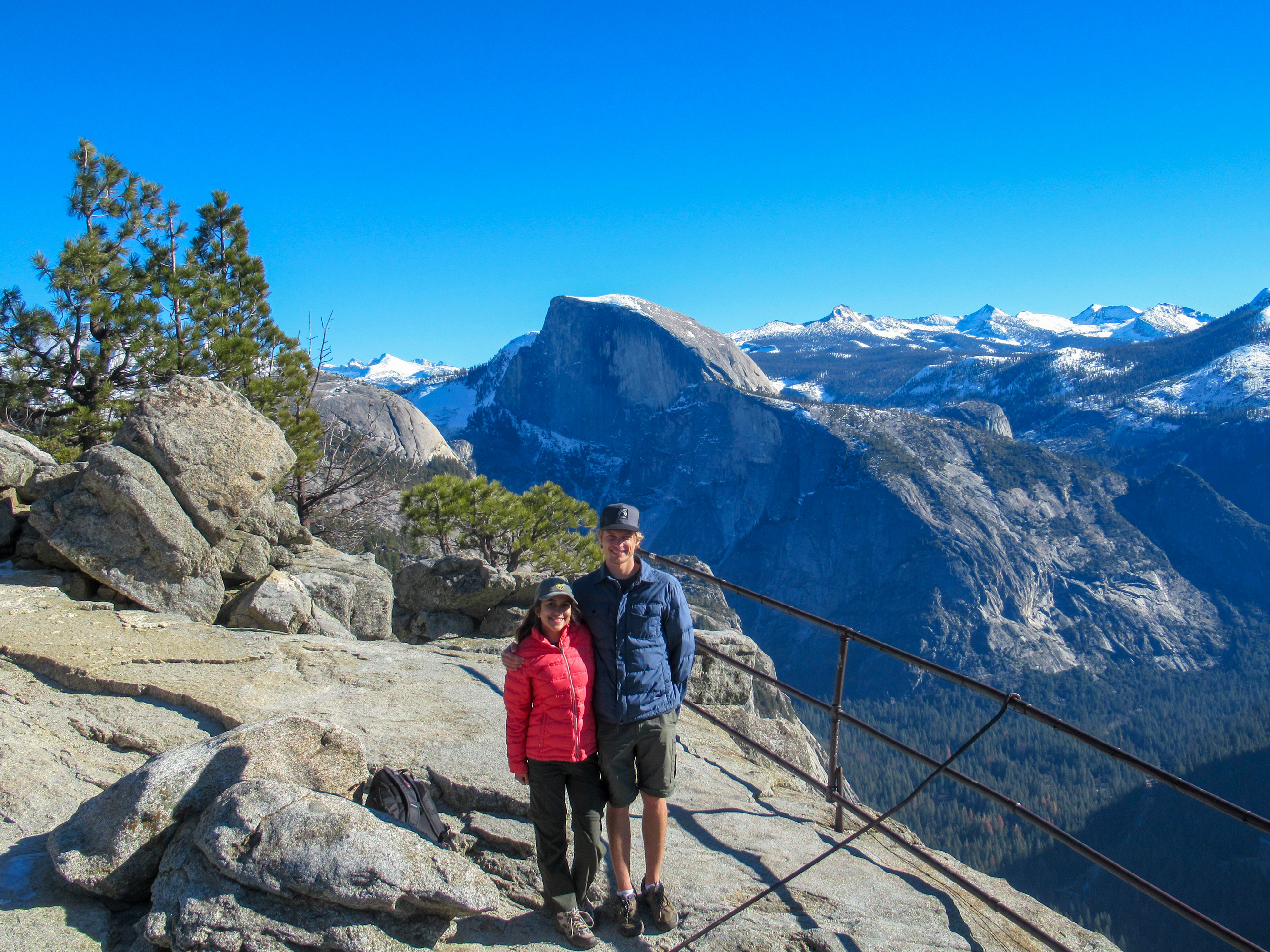 A couple takes a photo with Half Dome in the background.
