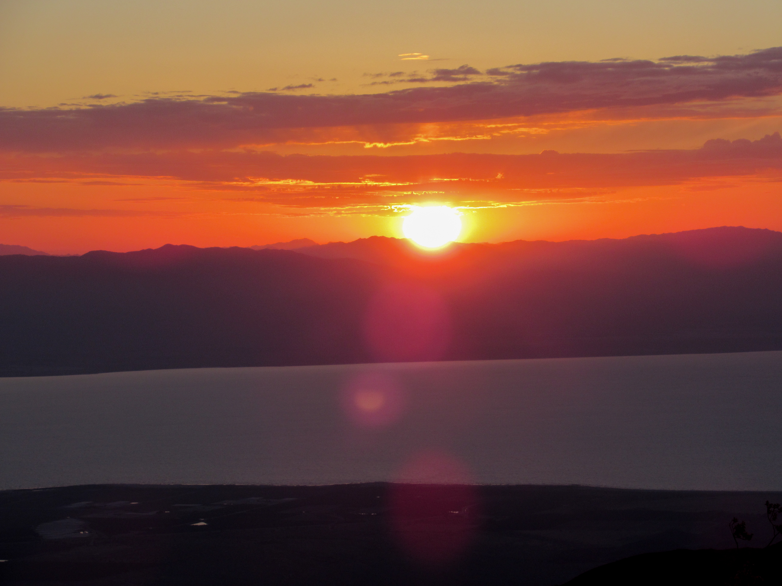 A red glowing sun rises above the Salton Sea.