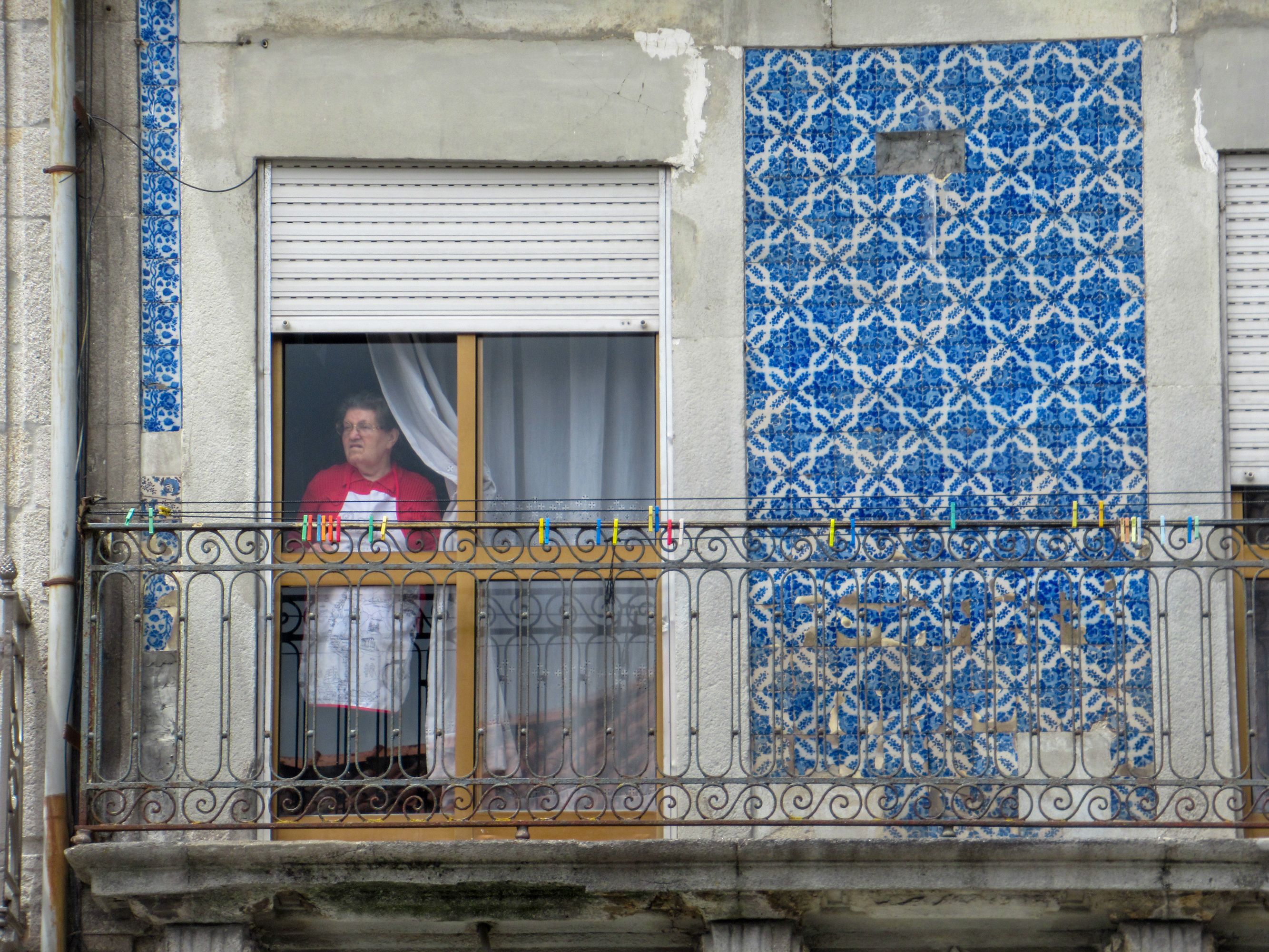 An old woman stares out her window in Portugal.