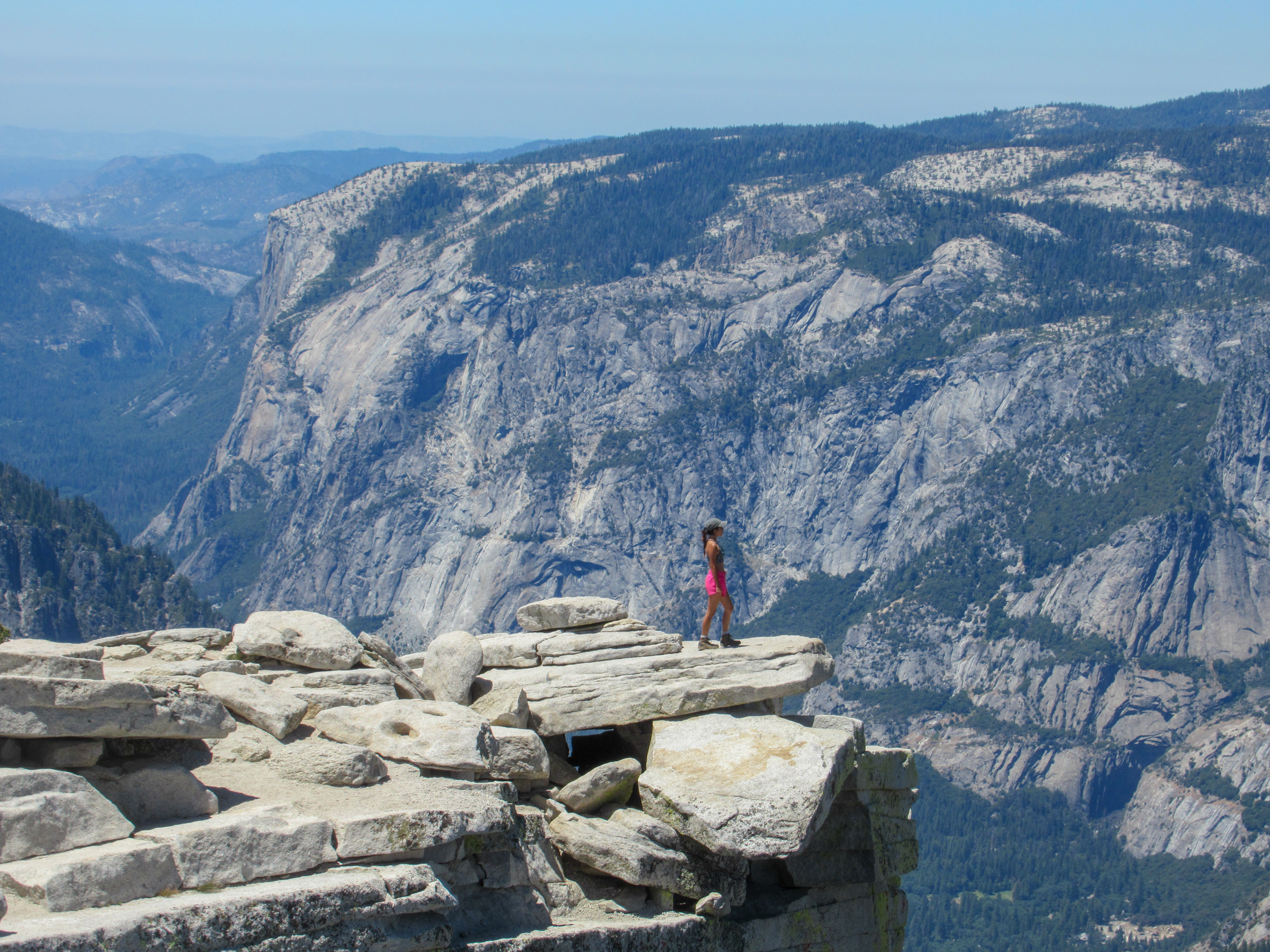 Madison Snively peers over the granite edge of Half Dome into Yosemite Valley.