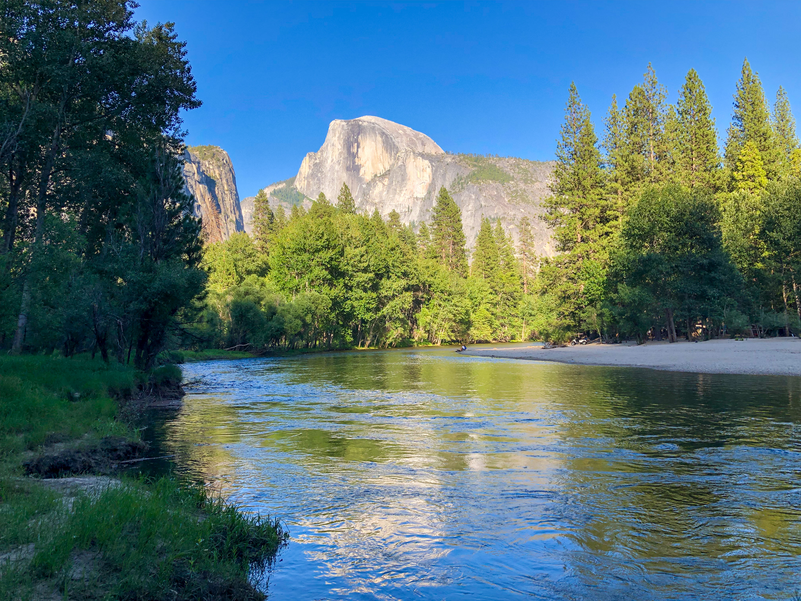 Sunshine illuminates Half Dome as seen from the Merced River in Yosemite Valley.