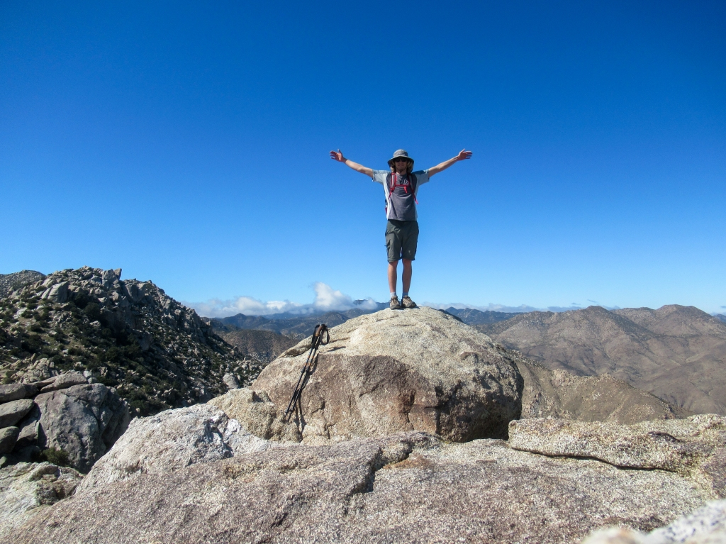 Evan Quarnstrom spreading his arms on the top of San Ysidro Mountain East.