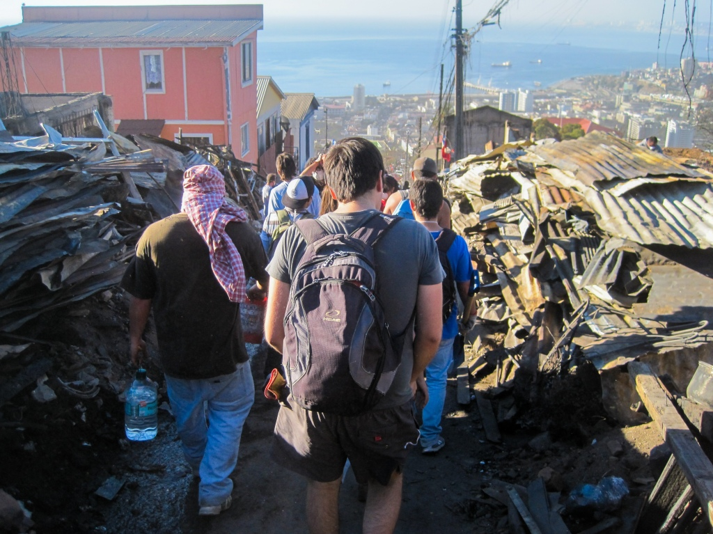 Volunteers help clean debris in the hills of Valparaiso, Chile after a fire broke out.