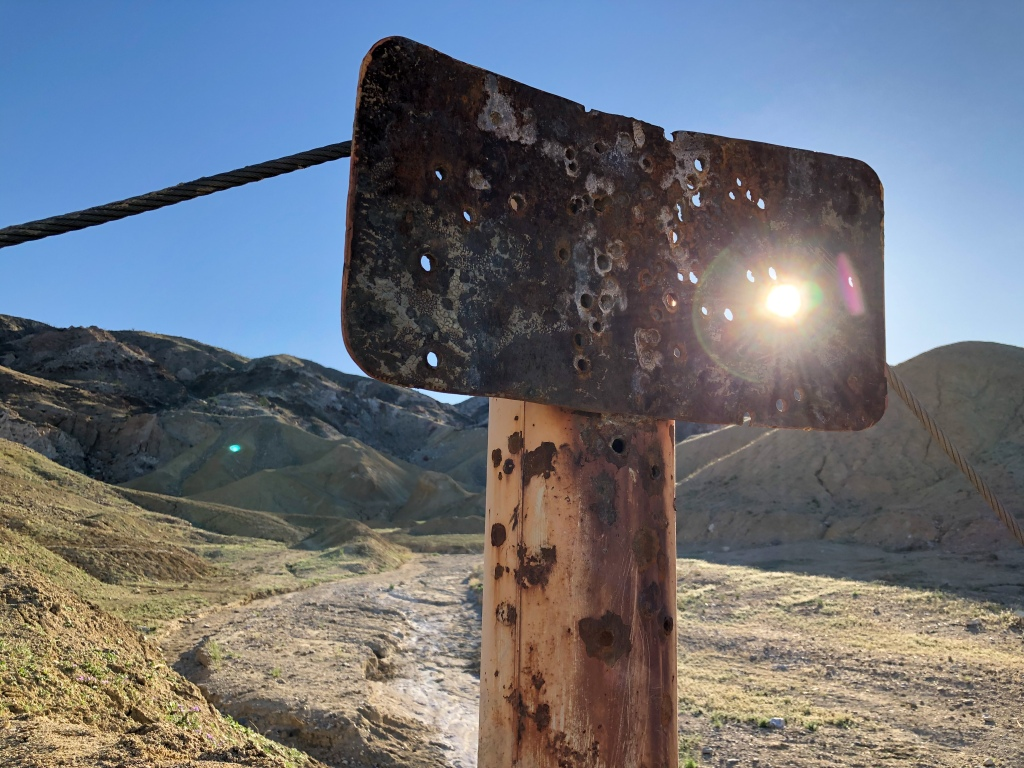 A trailhead sign covered in bullet holes in the California desert.