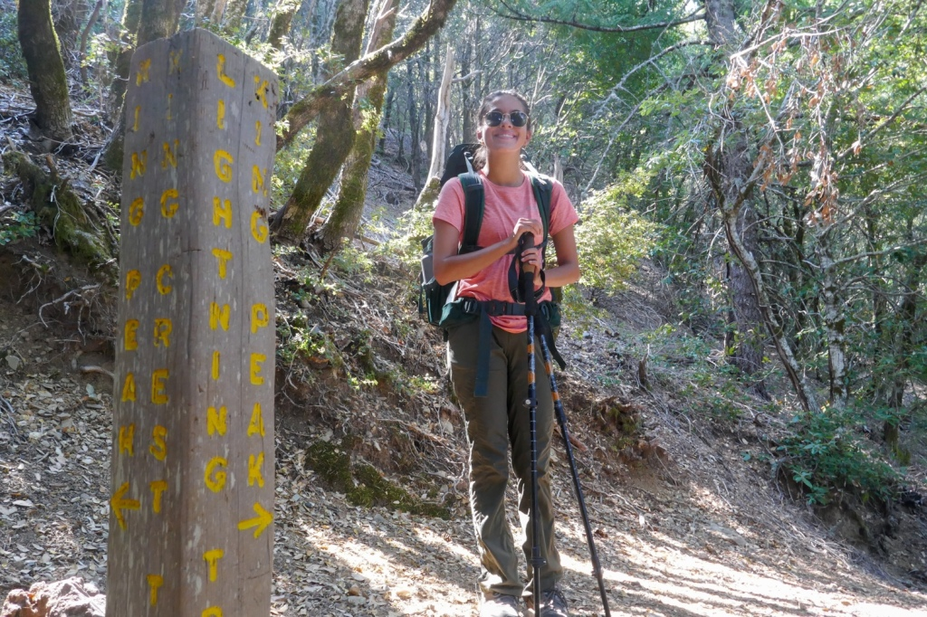 Madison Snively stands at a trail marker to King Peak.