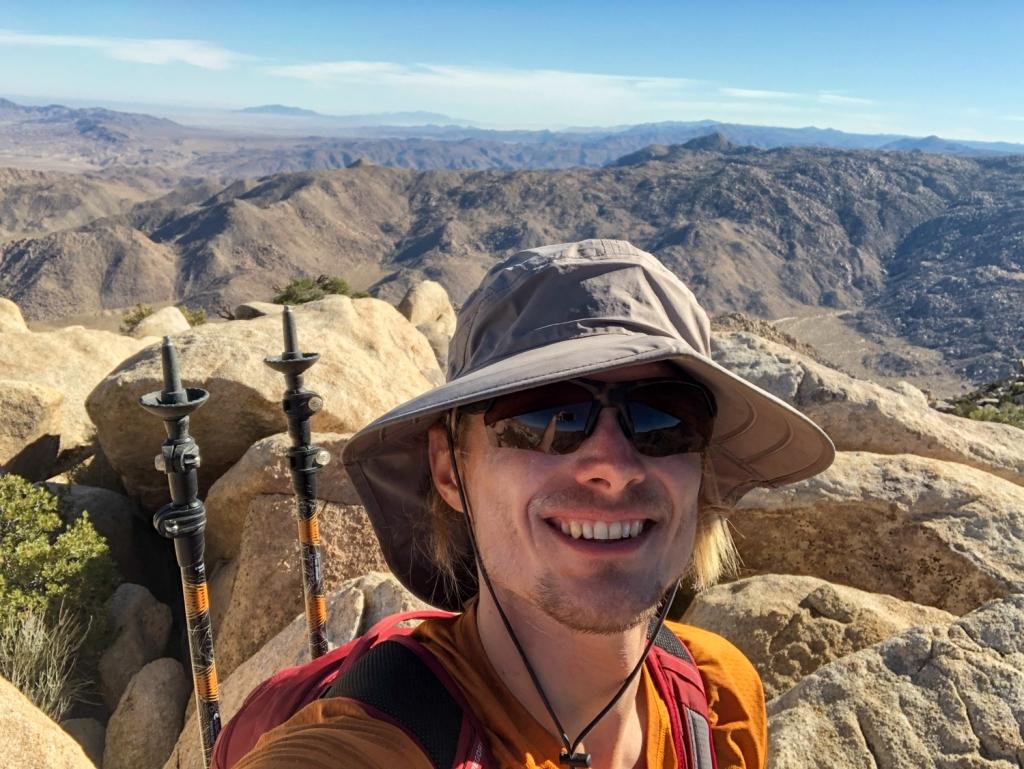 Evan Quarnstrom smiles stop Red Top peak.