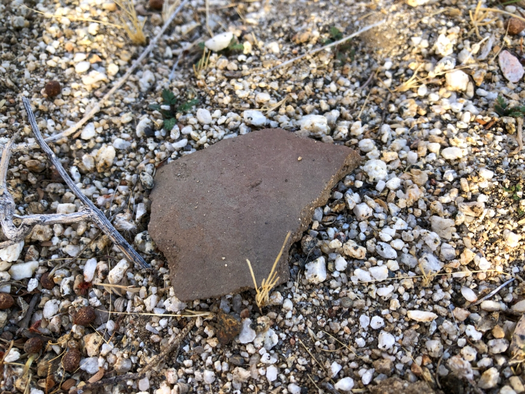 A Native American potsherd on the ground in the Californian desert.
